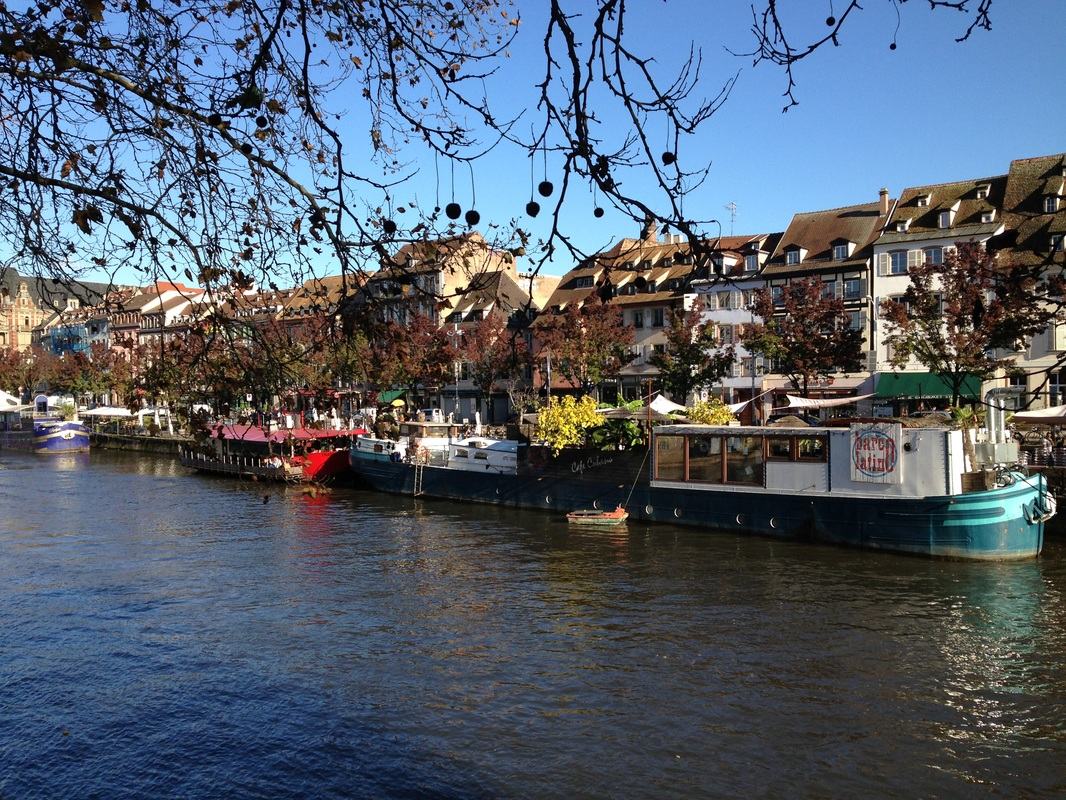 Colorful boats in the fall on the river in Strasbourg, France.